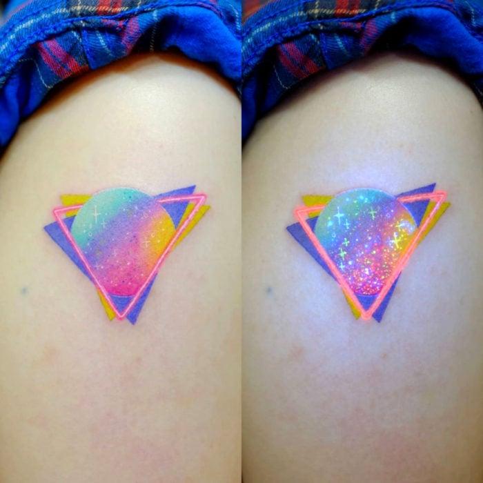 Tatuadora hace tatuajes bonitos, delicados y femeninos que brillan; tatuaje de planeta de colores pastel en el brazo