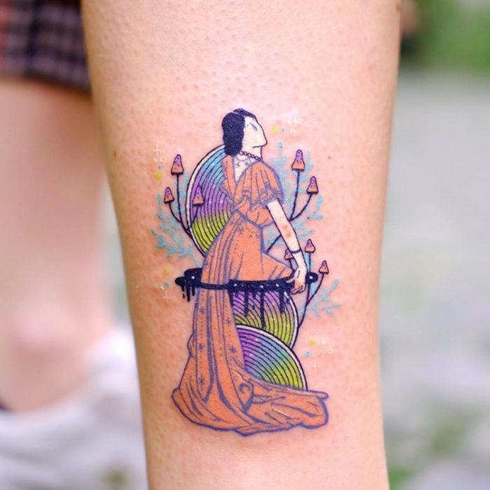 Tatuadora hace tatuajes bonitos, delicados y femeninos que brillan; tatuaje de mujer con flores y hongos y vestido