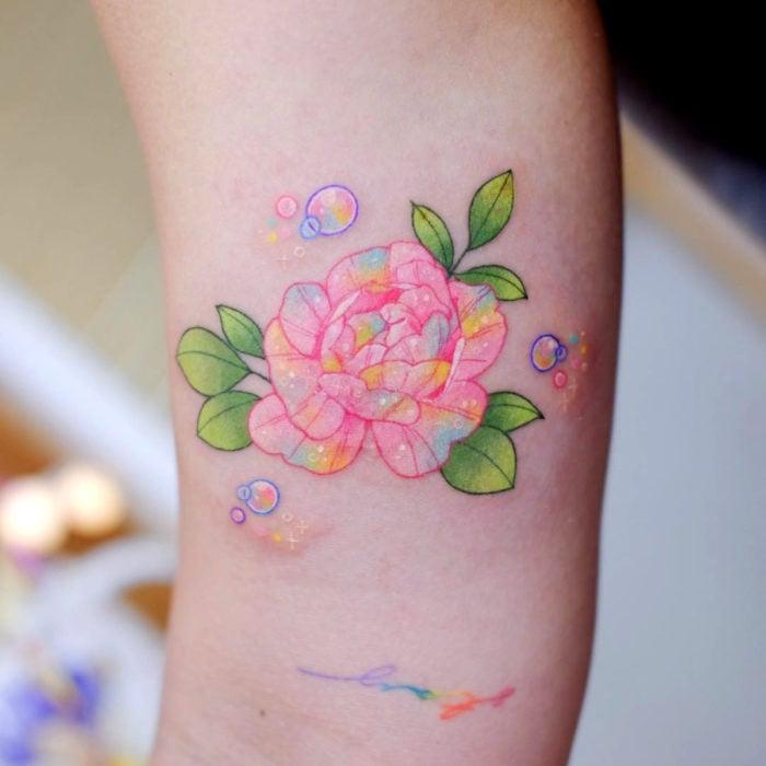 Tatuadora hace tatuajes bonitos, delicados y femeninos que brillan; tatuaje de flor peonia color rosa, amarillo y azul pastel en el brazo