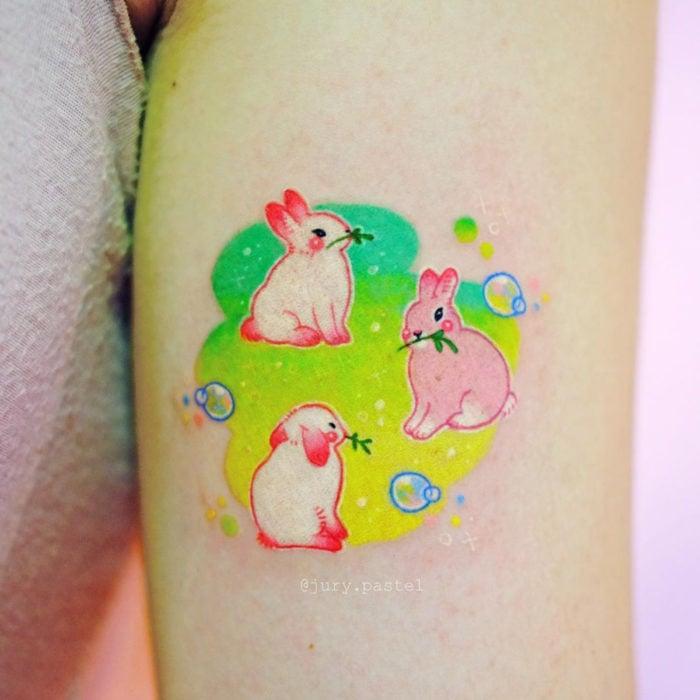 Tatuadora hace tatuajes bonitos, delicados y femeninos que brillan; tatuaje de conejos tiernos color rosa y blanco en el brazo