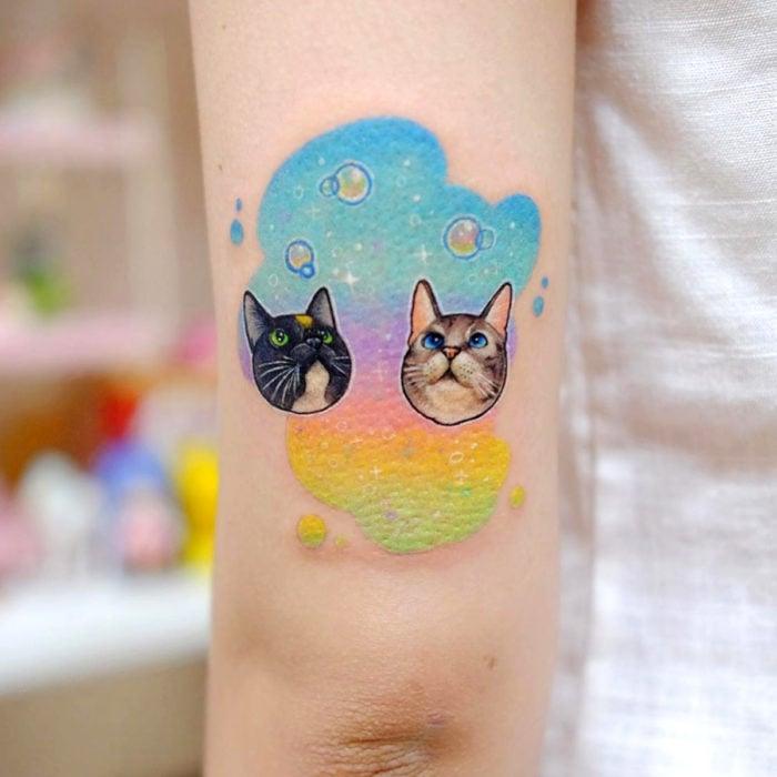 Tatuadora hace tatuajes bonitos, delicados y femeninos que brillan; tatuaje de gatos en arcoíris en el brazo