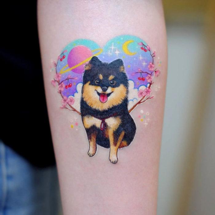 Tatuadora hace tatuajes bonitos, delicados y femeninos que brillan; tatuaje de perro con flores de cerezo, corazón con planetas y Luna en el brazo