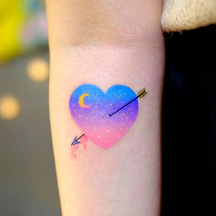 Tatuadora hace tatuajes bonitos, delicados y femeninos que brillan; tatuaje de corazón con flecha y Luna de colores azul, morado y rosa pastel en el brazo