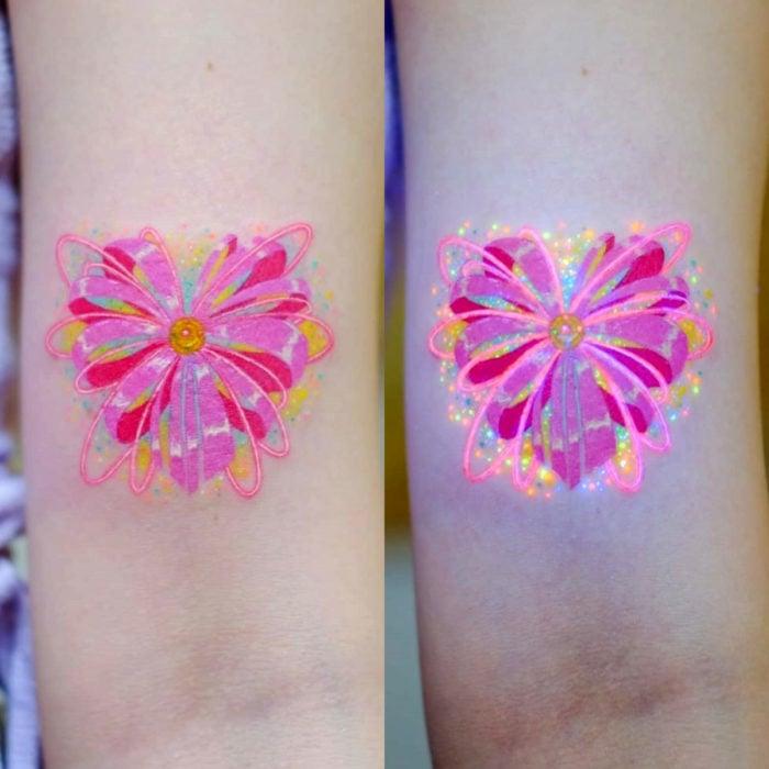 Tatuadora hace tatuajes bonitos, delicados y femeninos que brillan; tatuaje de corazón de listones de Sailor Moon color rosa en el brazo