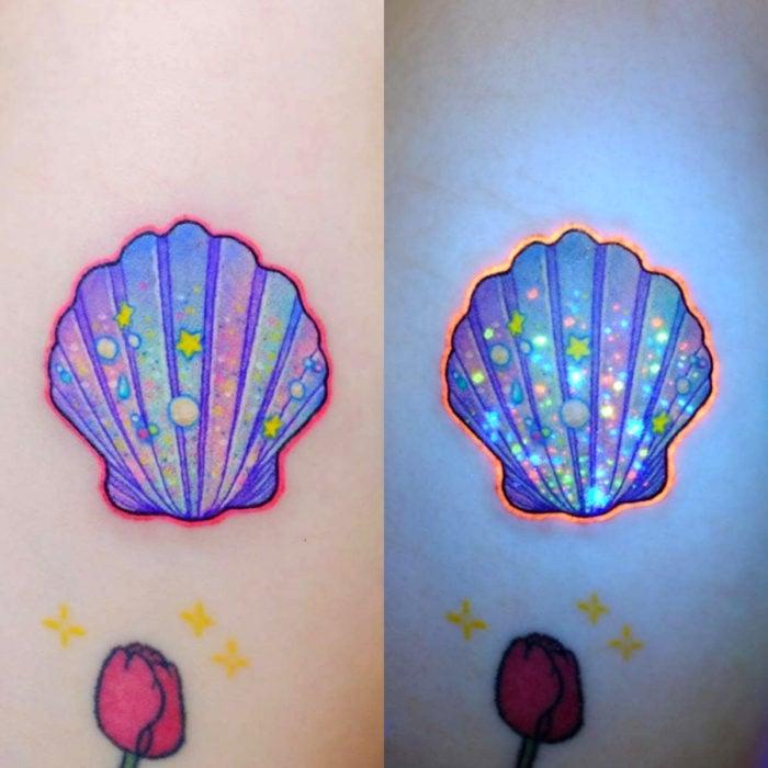 Tatuadora hace tatuajes bonitos, delicados y femeninos que brillan; tatuaje de concha de mar color azul, morado y rosa pastel en el brazo