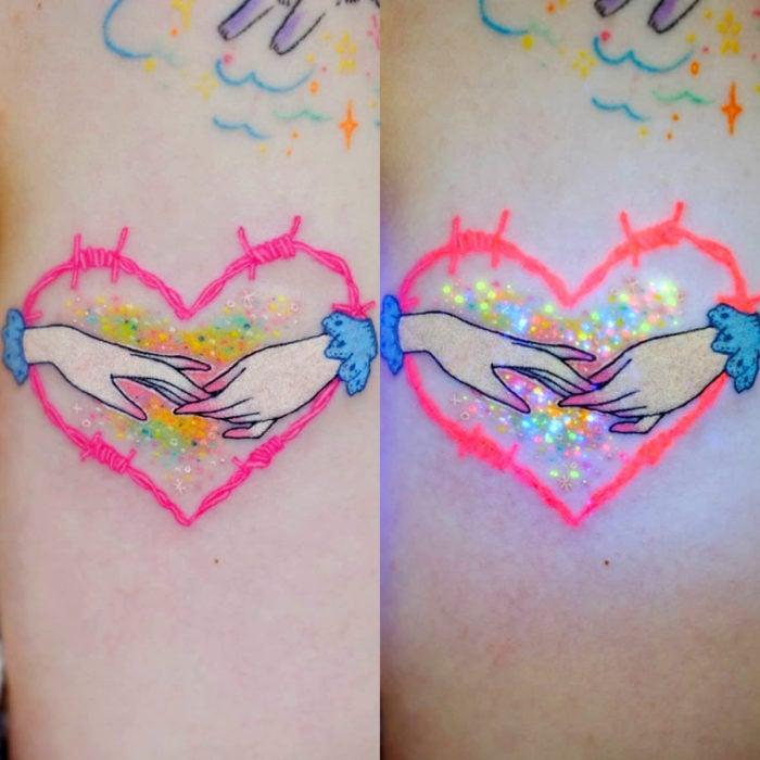 Tatuadora hace tatuajes bonitos, delicados y femeninos que brillan; tatuaje de manos con corazón de alambre de púas color rosa y azul pastel
