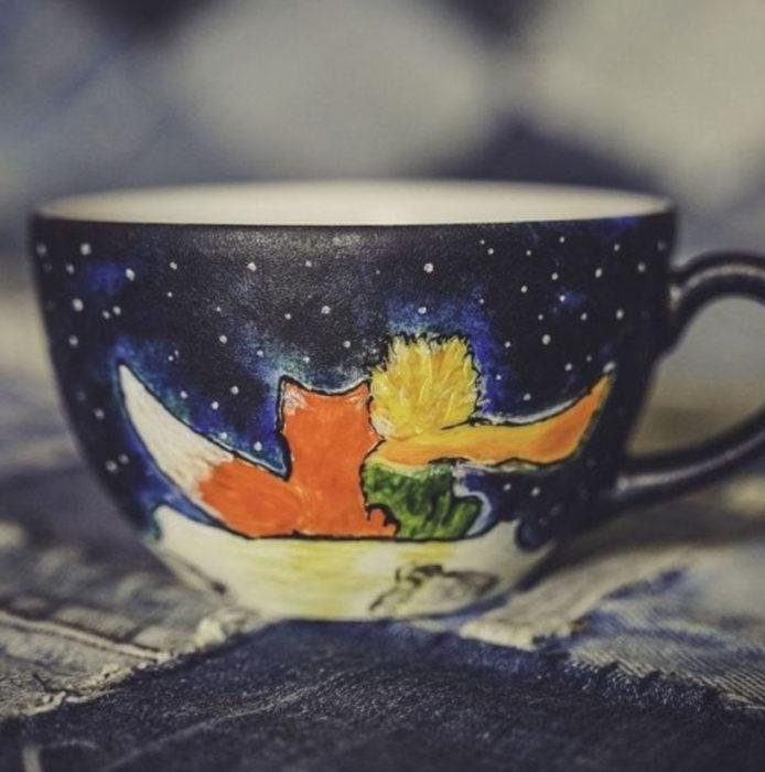 Taza inspirada en El Principito, donde se ve una noche estrellada y al Principito y al zorro viendo las estrellas