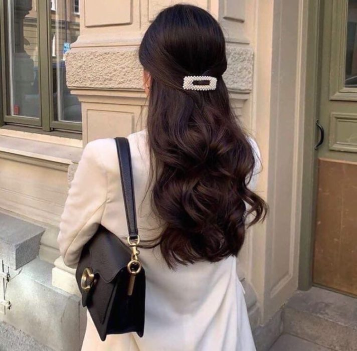 girl with long brown hair fastened with pearl brooch