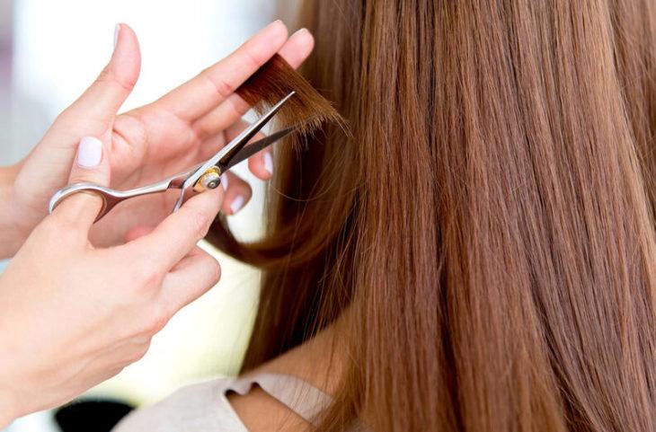 Manos despuntando cabello pelirrojo
