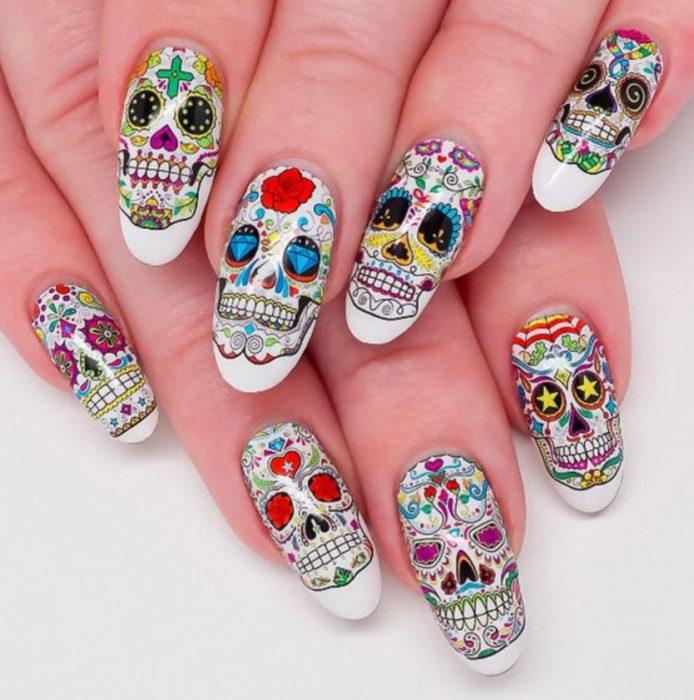 Uñas inspiradas en Día de Muertos con diseño de calaveras en cada uno de los dedos