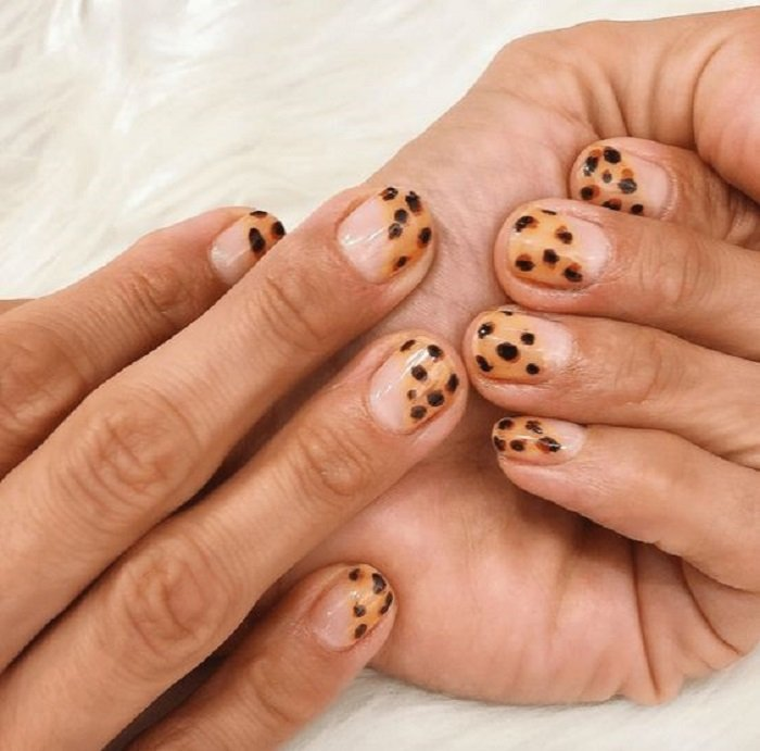 Manicure in animal print design on transparent base and mustard color with diagonal tip design on all fingers