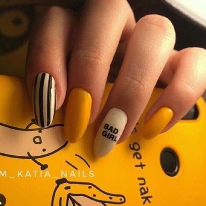 Mustard color manicure with black and white variation plus a little phrase