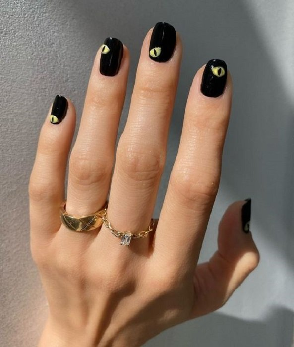 Manicure design on short nails in black and eyes painted on them