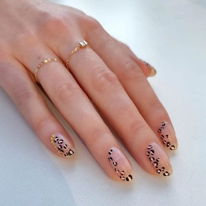 Manicure in animal print design on transparent base and design on the lateral side on all fingers