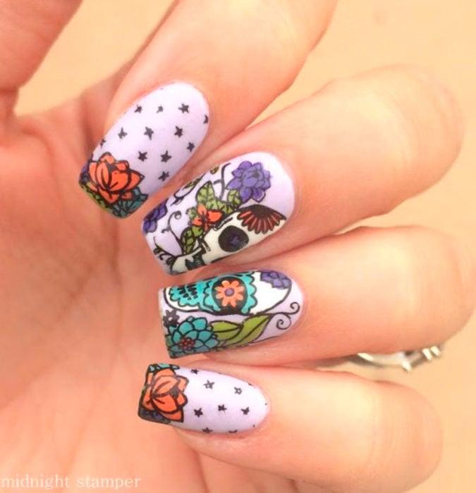Uñas inspiradas en Día de Muertos con diseño de calaveras con flores de cempasúchil