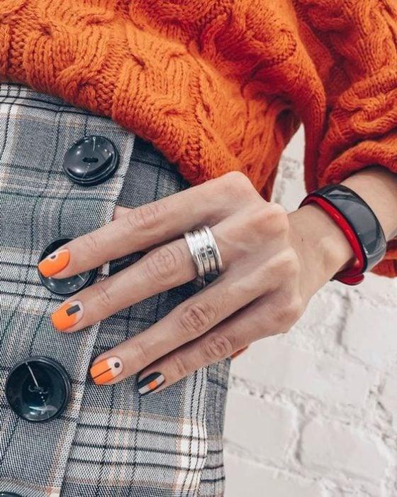 Manicura con detalle geométrico en color naranja y negro