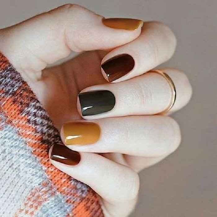 Manicure in mustard color with variation of brown and green colors