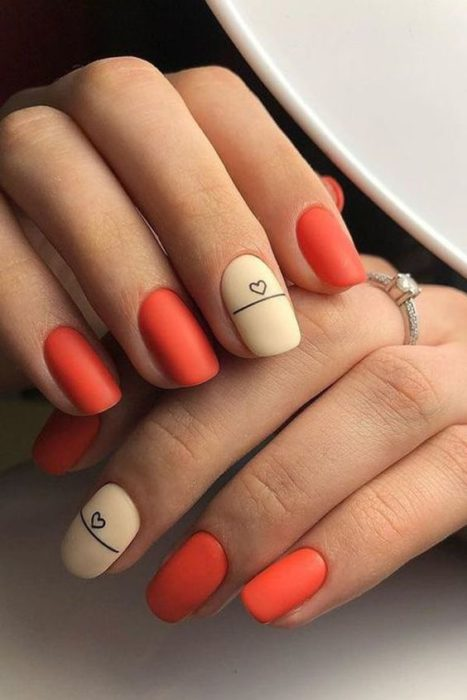 Manicure design on short red nails with a beige nail and black detail in matte effect