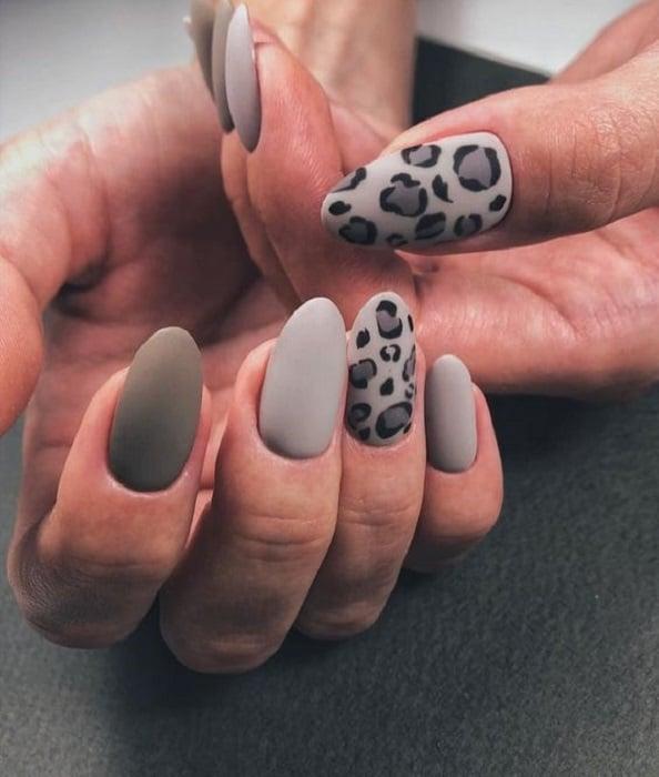 Manicura en diseño animal print en colores grises con el dedo anular y pulgar decorados