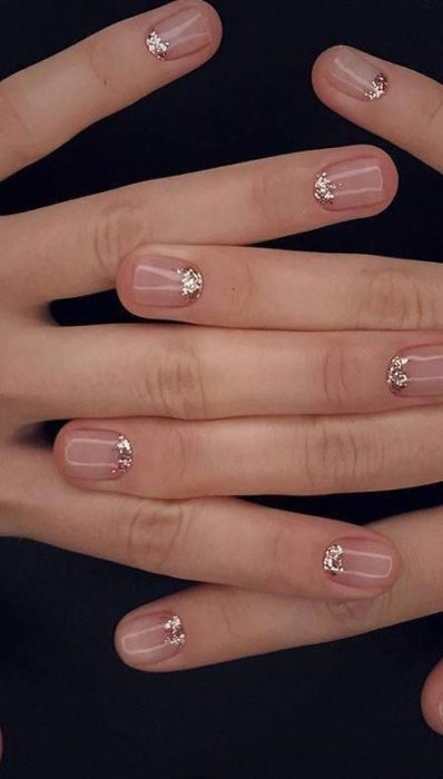 Manicure design on short transparent nails with the moon area in gold