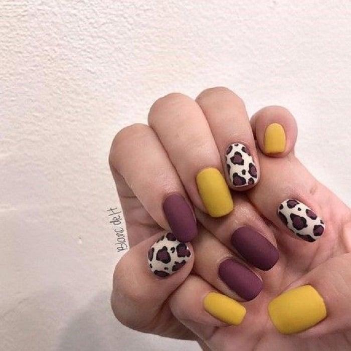 Manicura en diseño animal print en colores vino, mostaza, con los dedos pulgar y anular decorados