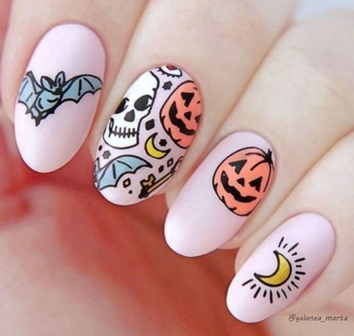Uñas inspiradas en Halloween con diseño de color rosa, calaveras, murciélagos y calabazas