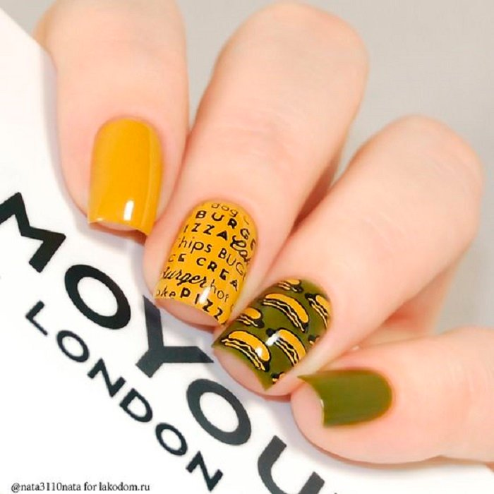 Manicure in mustard color with design of letters on one finger, olive green tone and drawn hot dogs