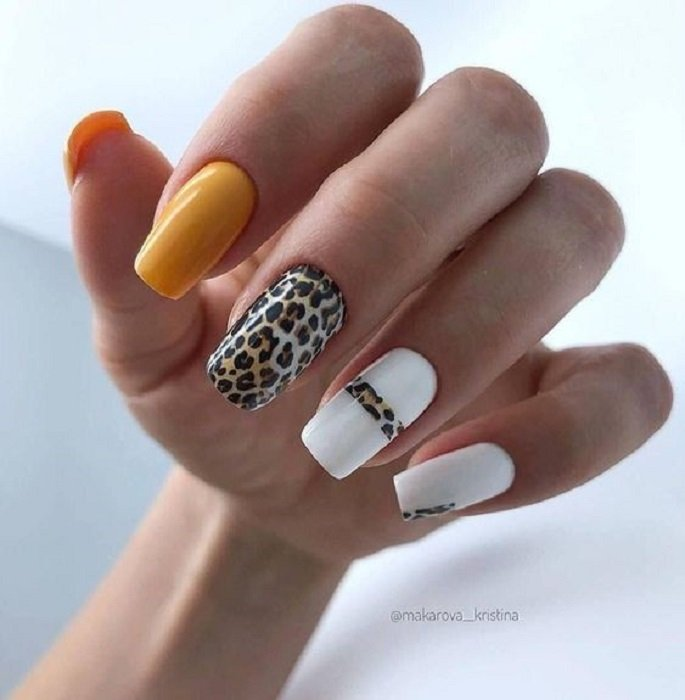 Manicure in animal print design in orange, yellow and white, with the middle and ring finger with said design