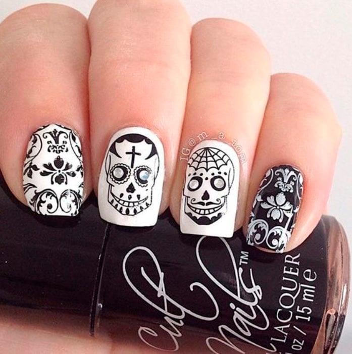 Uñas inspiradas en Día de Muertos con diseño de calaveras en color blanco y negro