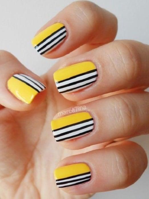 Manicura con detalle geométrico en colores amarillo, nergro y blanco