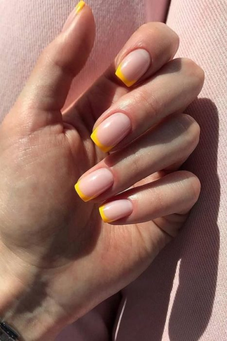 Manicure design on short nails on nude background and French type in yellow color