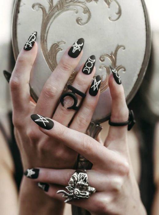 Uñas inspiradas en Halloween con diseño de símbolos de brujas