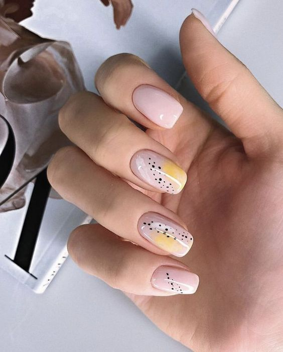 Manicure in mustard color with a nude background and black dots