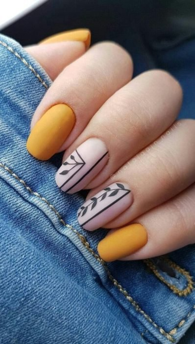 Mustard color manicure with other designs on beige background and black lines in matte effect