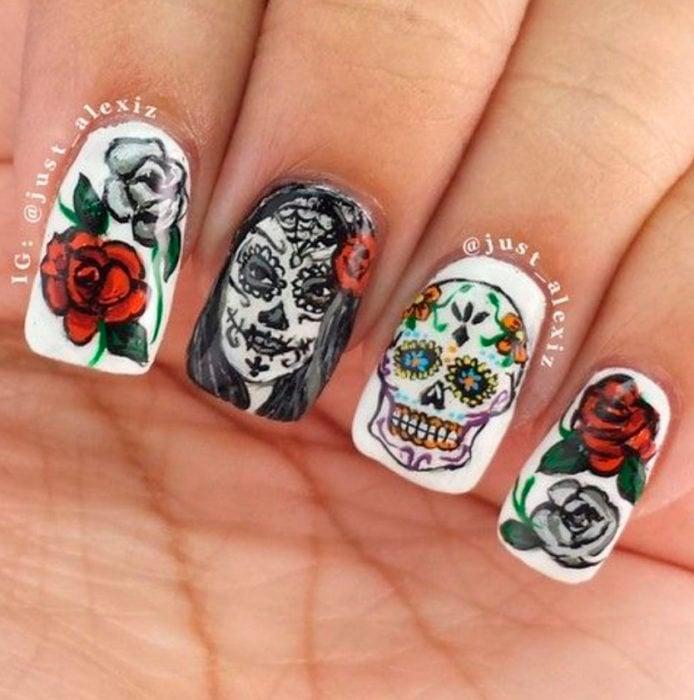 Uñas inspiradas en Día de Muertos con diseño de calaveras y rosas