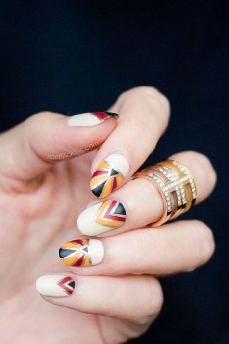 Manicure in mustard color with a white background and in black, red and gold geometric figures