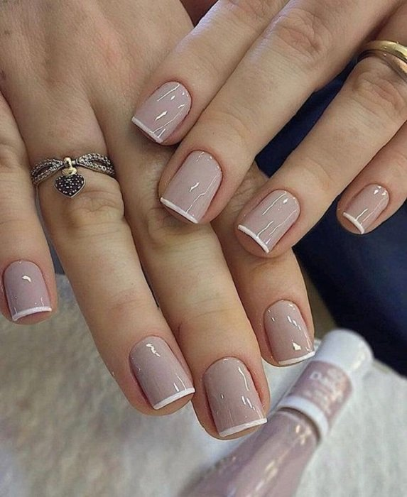 Manicure design on short nails on nude background with white french