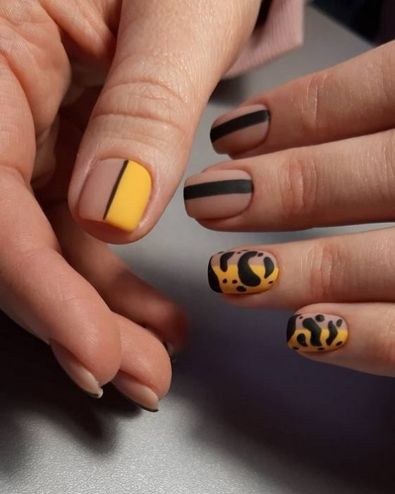Manicure in animal print design in black and mustard colors with matte effect