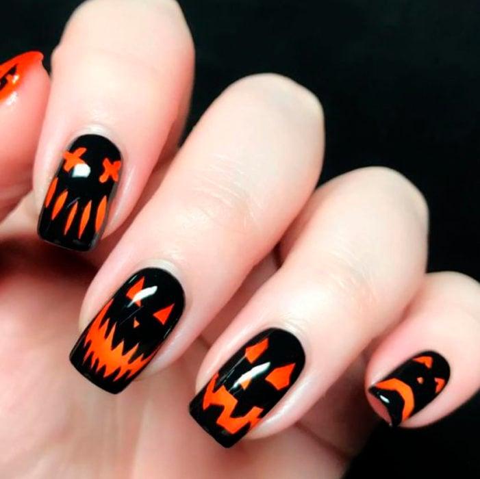 Uñas inspiradas en Halloween con diseño de calabazas con diferentes rostros