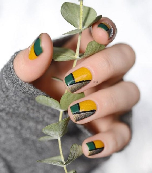 Manicure in mustard color with gold, green and black lines