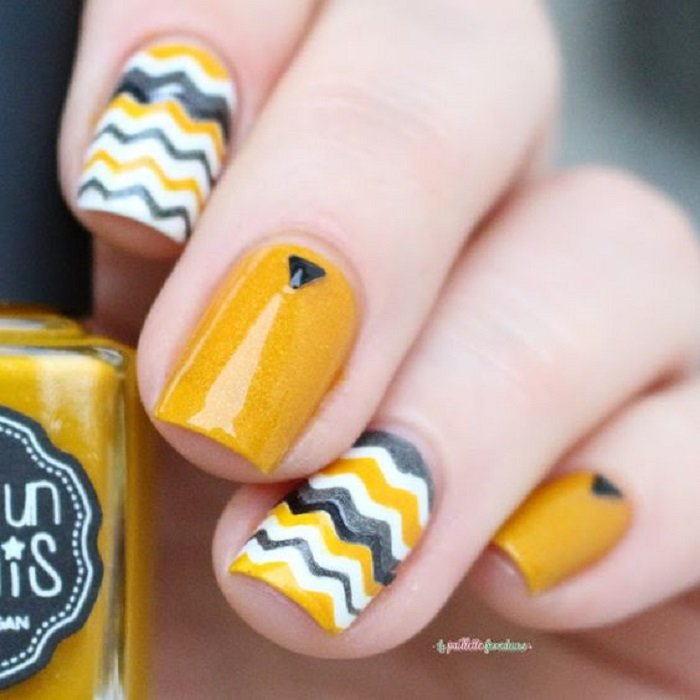 Mustard manicure with a pebble and line design in other colors