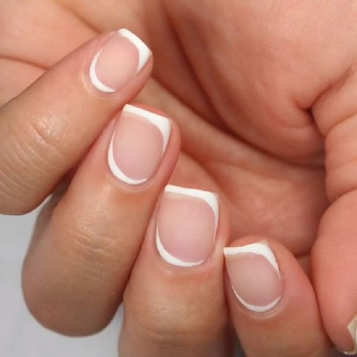 Manicure design on short nails in transparent color and around white