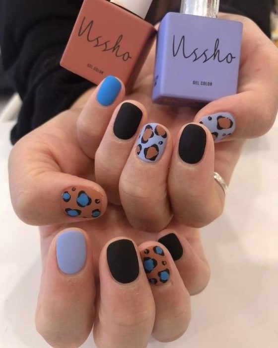 Manicure in animal print design in blue and black colors with design on thumb and middle fingers