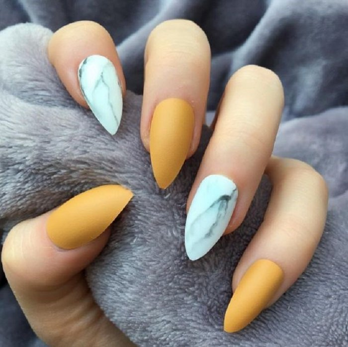 Manicure in mustard color with nails in white marble tone all in matte effect