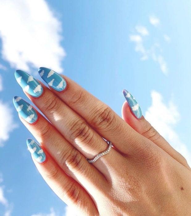 Manicura con diseño de cielo y nubes; uñas en forma de almendra pintadas con esmalte azul
