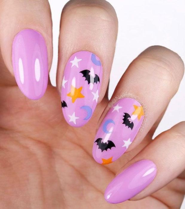 Diseños de uñas largas almendra kawaii, tiernas en color rosa pastel de Halloween; murciélagos, lunas y estrellas