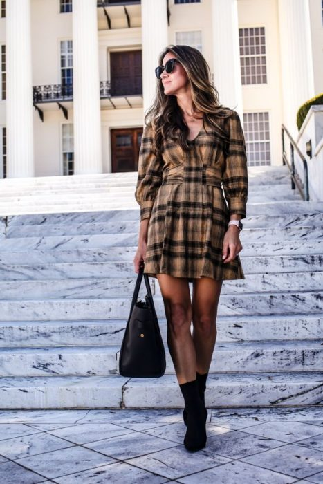 Girl wearing black tights, ankle boots and bag and long sleeve short plaid brown dress