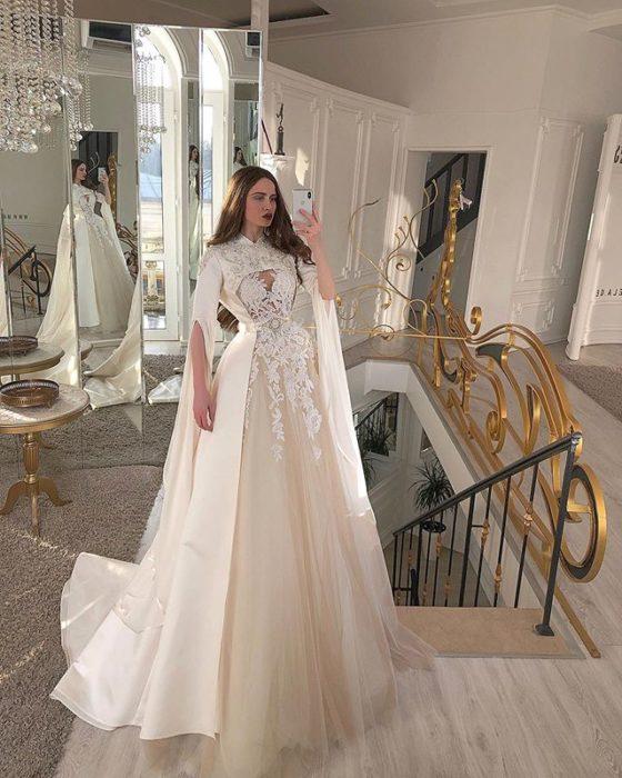 Chica con vestido de novia diseñado por Marionela con mangas amplias y abertas