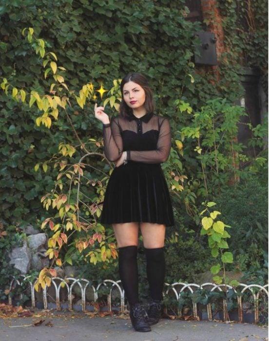 chica posando con vestido y botas negras