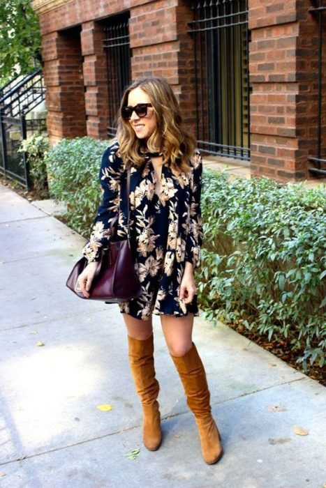 Brown haired girl wearing sunglasses and navy blue floral dress with camel boots